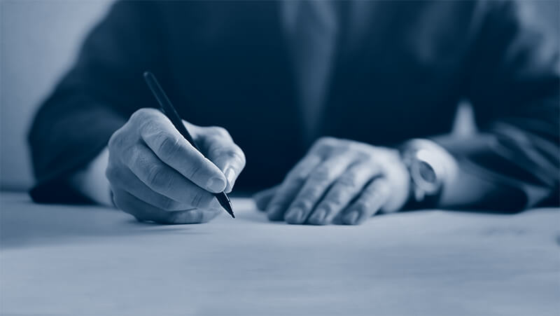 Film financing executive signs paperwork on a production loan.